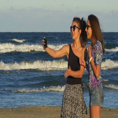 Two teenage girls enjoying a beautiful summer day and having video call on smart Stock Footage