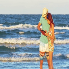 Romantic couple kissing at the seaside and holding a tablet pc Stock Footage