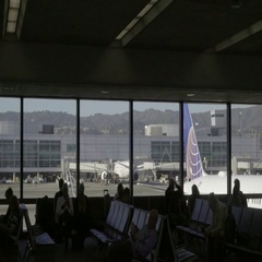 Newark EWR Airport interior with large windows behind travelers and passengers Stock Footage