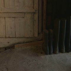 A man in rubber boots comes in with a basket of harvest and enters the barn, 4K Stock Footage