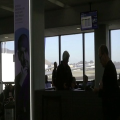 Man checking smartphone texting on cell phone walking interior Newark Airport Stock Footage