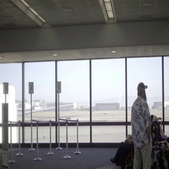 Man looking out window in airport interior talking cell phone tracking travelers Stock Footage