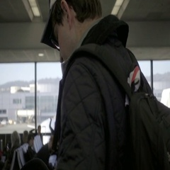 Tracking shot inside Newark Airport, people sitting in chairs waiting for flight Stock Footage
