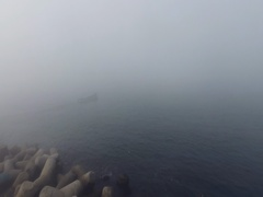 Boat on foggy sea water near the coast, aerial video Stock Footage