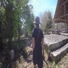 Gimbal shot of tourist woman walking in Ek Balam Mayan Ruins Stock Footage