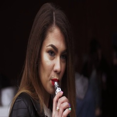 Girl with red lips exhalation steam from electronic cigarette on street. Vaper Stock Footage