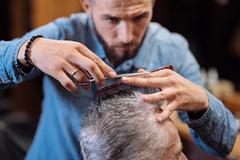 Close up of young male hairdresser cutting hair Stock Photos
