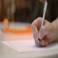 Hand is writing Christmas mail. Blurred lights on background 4k UHD (3840x2160) Stock Footage