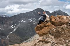 Tourist with a backpack sitting on top of  mountain and taking pictures  the Stock Photos