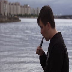 Young man exhalation steam from electronic cigarette at water. Vaper. City Stock Footage