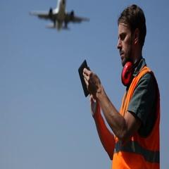 Airport Crew Member Man Work a Digital Tablet Airplane Vehicle Passing Overhead Stock Footage