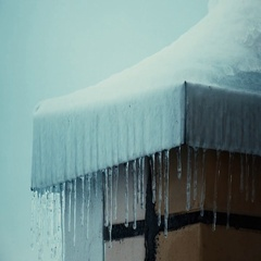 Multiple icicles and snowy sloped roofs of residential houses in winter 4K Stock Footage