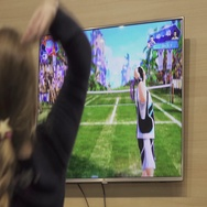 Girl playing virtual tennis game on a big screen. Stock Footage