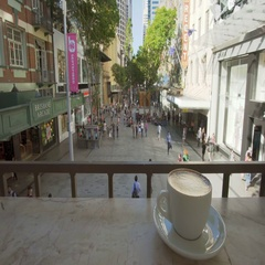 Enjoying coffee in a cafe in pedestrian mall Stock Footage