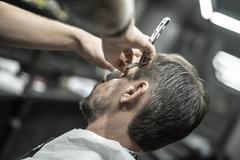 Trimming beard in barbershop Stock Photos