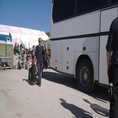 LESVOS, GREECE - NOV 5, 2015: Boarding the bus to the refugee camp Stock Footage