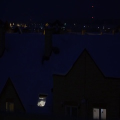 Snowy sloped roofs of residential houses at night Stock Footage