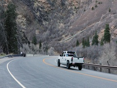 Truck drives down mountain canyon motorcycle parked DCI 4K Stock Footage