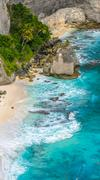 Rock in the ocean with palms behind at Atuh beach, Nusa Penida, Indonesia. Stock Photos