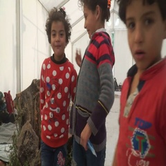 LESVOS, GREECE - NOV 5, 2015: Refugee kids look at the camera inside a tent in Stock Footage