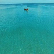 Aerial: Flying over the sea towards the long tail boat. Stock Footage
