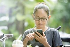 Young Asian woman  using smartphone in garden, looking on screen. Stock Photos