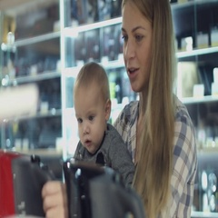 Family with baby son choosing household appliances in the store Stock Footage