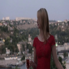 Seductive blonde in the red evening dress drinking champagne on the outdoors Stock Footage