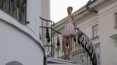 Brunette in a short pale pink dress with a fluffy skirt posing on a ladder Stock Footage