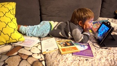 Child watches tablet on sofa Stock Footage