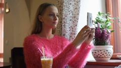 Pretty girl doing selfies on smartphone and checking them while sitting in the c Stock Footage