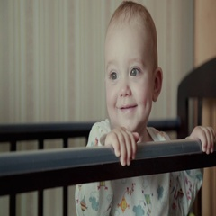 The Kid Stand Up By Legs And Smiles In The Bed Stock Footage