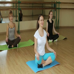 Beautiful girl sitting in Lotus pose in the gym. Woman resting after a workout. Stock Footage