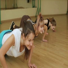 Three young healthy girls press from the floor on my knees in the gym. Stock Footage