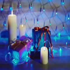 Gift boxes and candles with bright blue garland. Concept christmas and new year Stock Footage