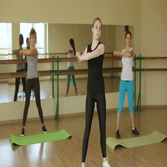 A group of girls doing warm-up before training in the gym with a big mirror. Stock Footage