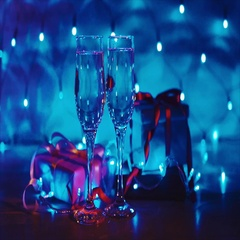 Close up of xmas and new year presents, two glasses champagne with blue garland Stock Footage