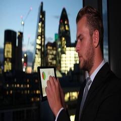 Businessman Using Digital Tablet Analyzing Pie Chart Sales Report London Skyline Stock Footage