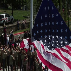 Boy Scouts holding American Flag as it is being strung up a pole. Stock Footage