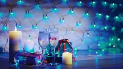 Christmas presents, candles and two glasses of champagne blue garland background Stock Footage