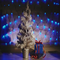 Present under the small silver Christmas tree blue garland background. Stock Footage