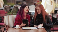 Two frends girls laughting in cafe using tablet pc Stock Footage