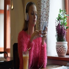 Pretty girl enjoying listening music and drinking juice while using smartphone Stock Footage
