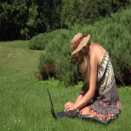 Amused blonde woman with hat working with her notebook sitting on lawn in sunny Stock Footage