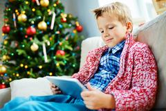Little boy with touchpad sitting at home by Christmas tree Stock Photos