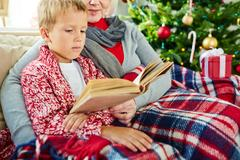 Adorable kid reading stories in book with his grandmother Stock Photos