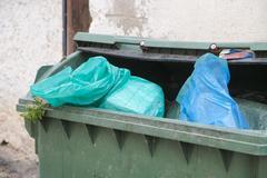Green trash dumpster full of garbage Stock Photos