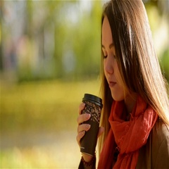 Beautiful Young Caucasian Woman Drinking Takeaway Coffee in Autumn Park. Pretty Stock Footage