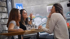 Three beautiful girls are having coffee break together, talking and laughing. Stock Footage