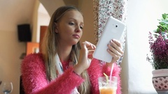 Pretty, stylish girl browsing internet on tablet while sitting in the cafe Stock Footage